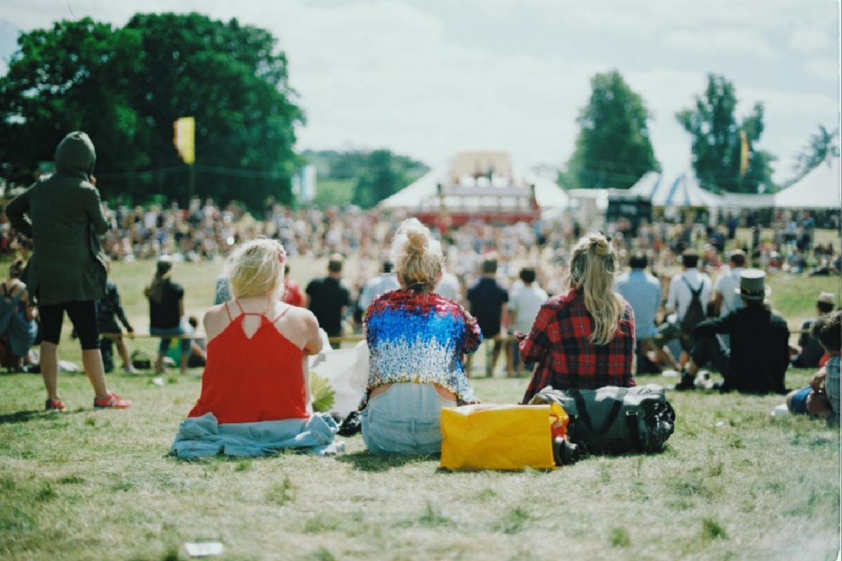 Menschen sitzen auf Festivalgelände