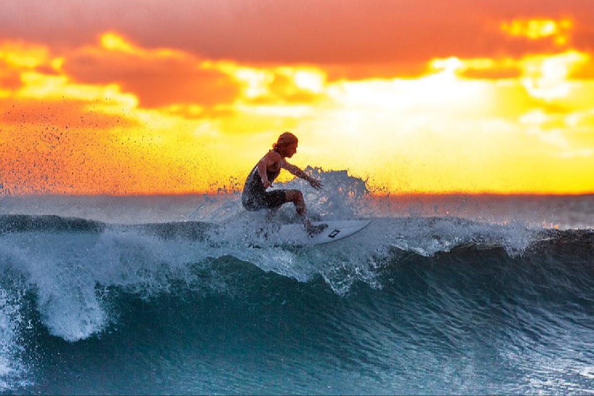 Frau surft im Sonnenuntergang