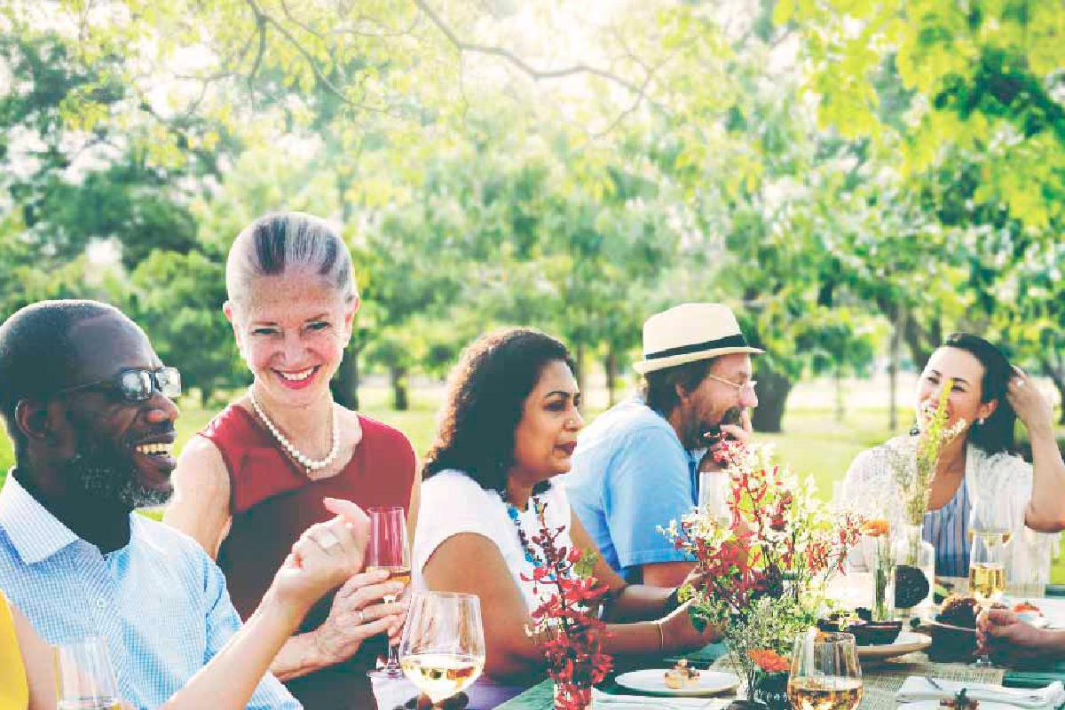 Sitzende Menschen essen und lachen draußen
