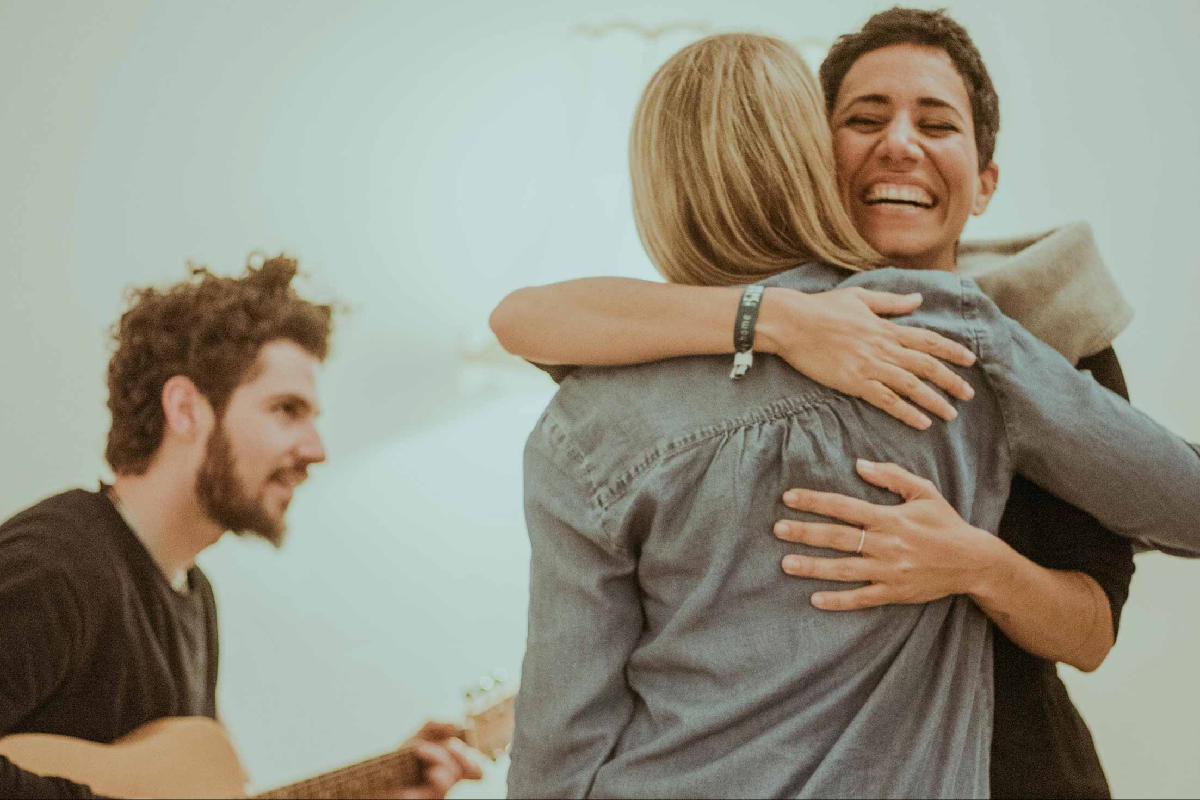 Frauen umarmen sich vor Musiker