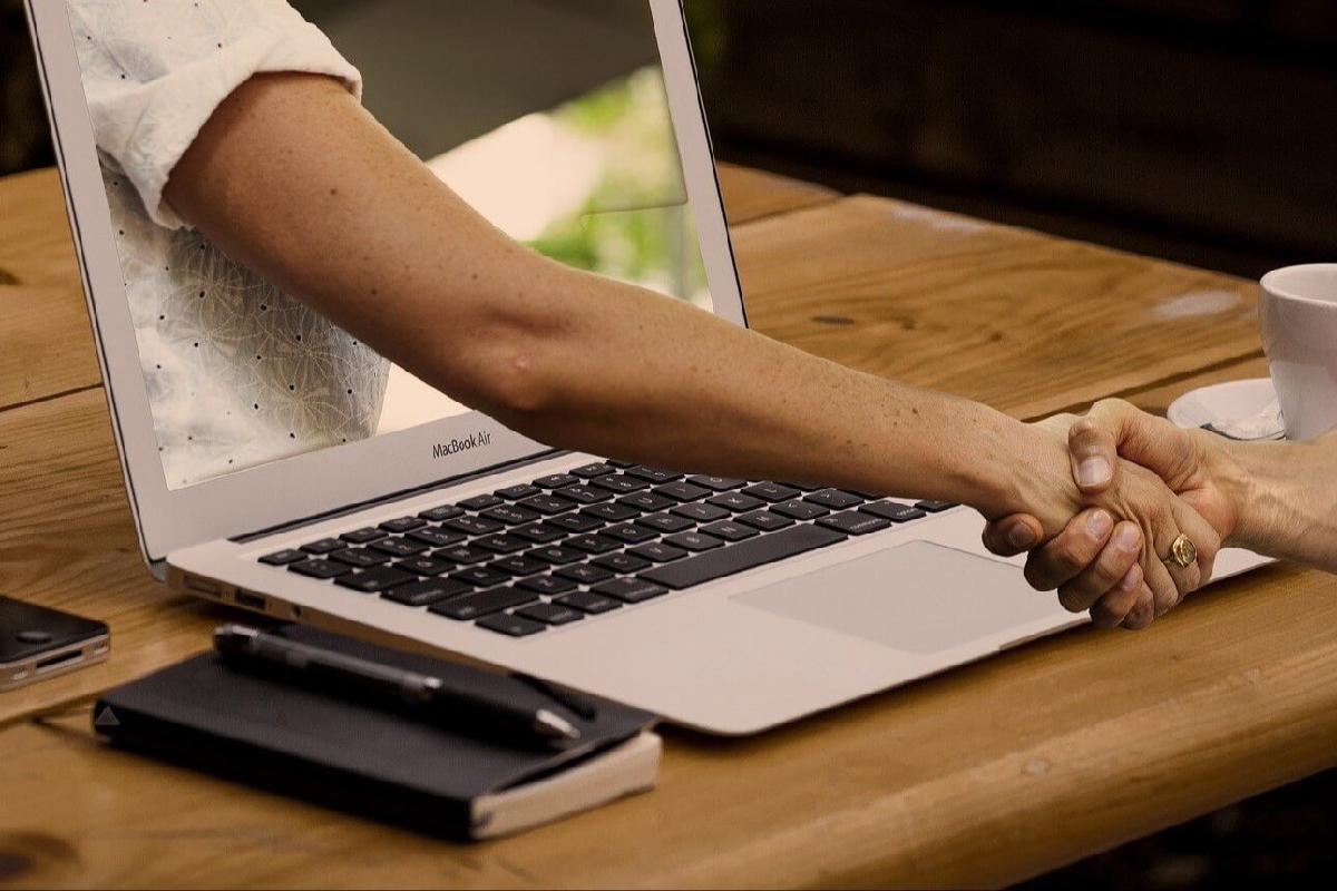 Zwei menschen schütteln sich die Hände durch einen Laptop hindurch