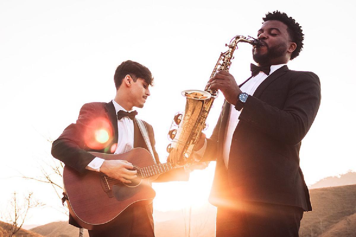 Zwei Musiker mit Instrumenten spielen auf einer Wiese