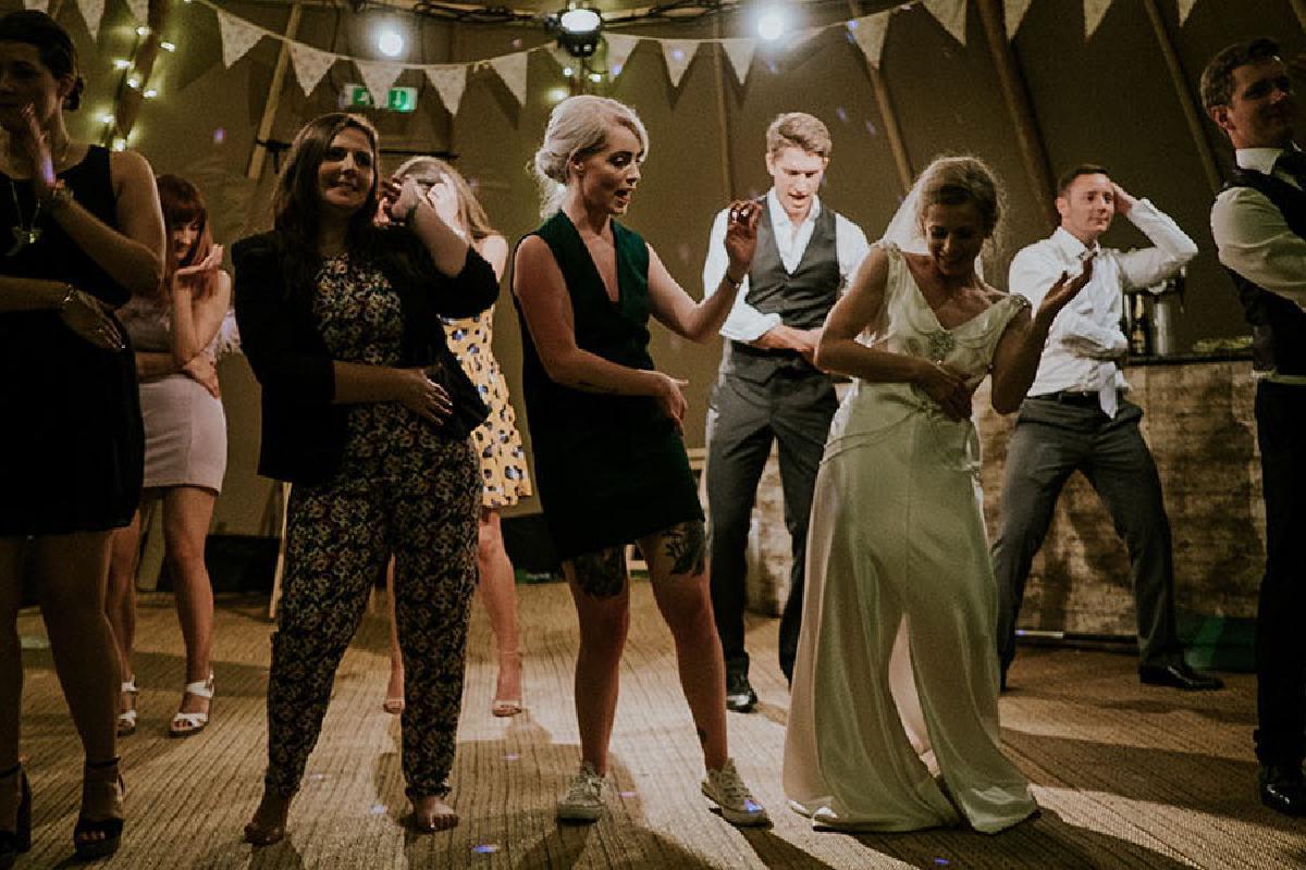 Ehepaar und Gäste tanzen auf Hochzeit
