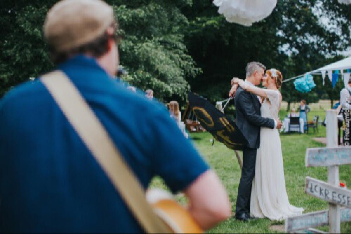 Künstler spielt Gitarre für Ehepaar auf Hochzeit