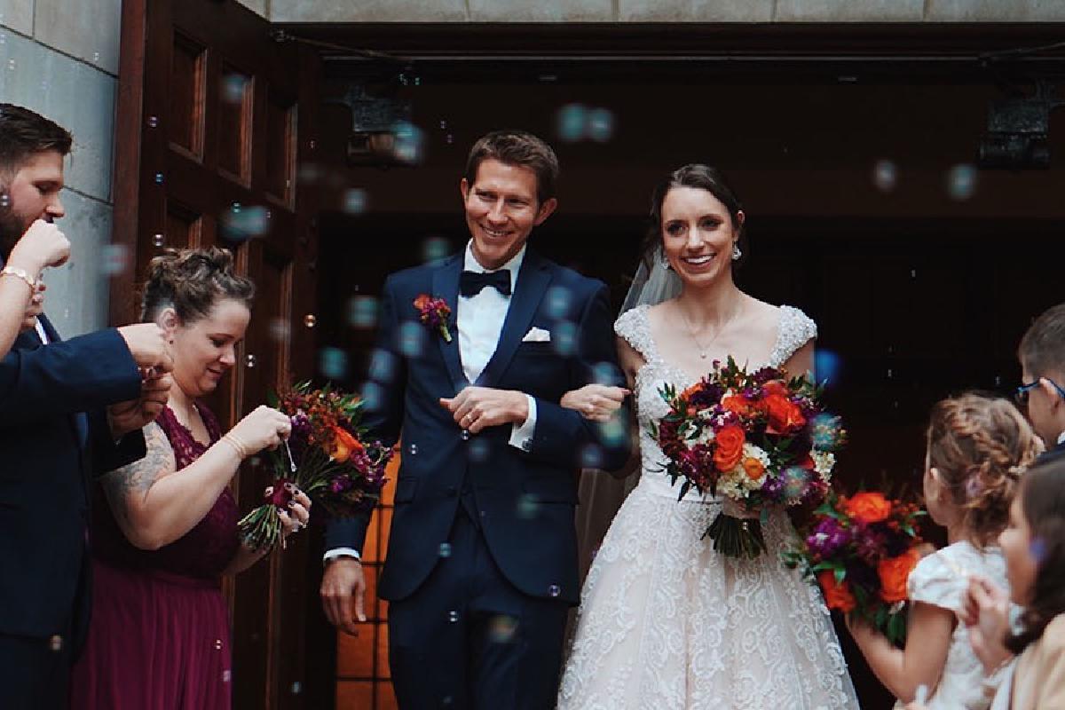 Ehepaar zieht aus der Kirche und Gäste jubeln