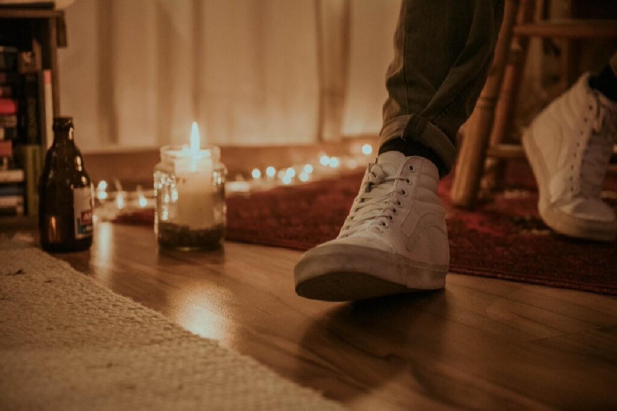 Kerze und Bierflasche auf Boden
