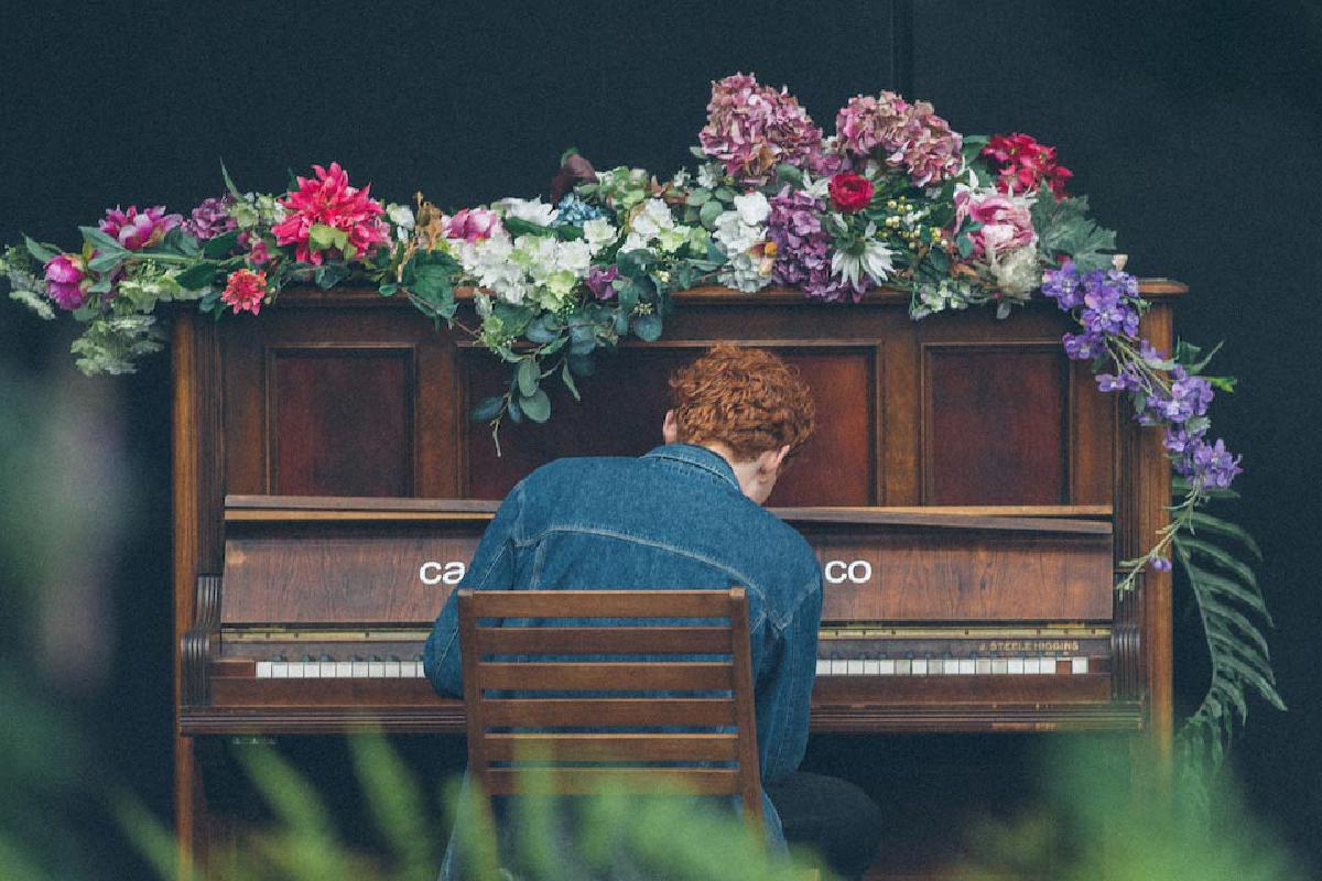 Mann spielt blumenbedecktes Klavier