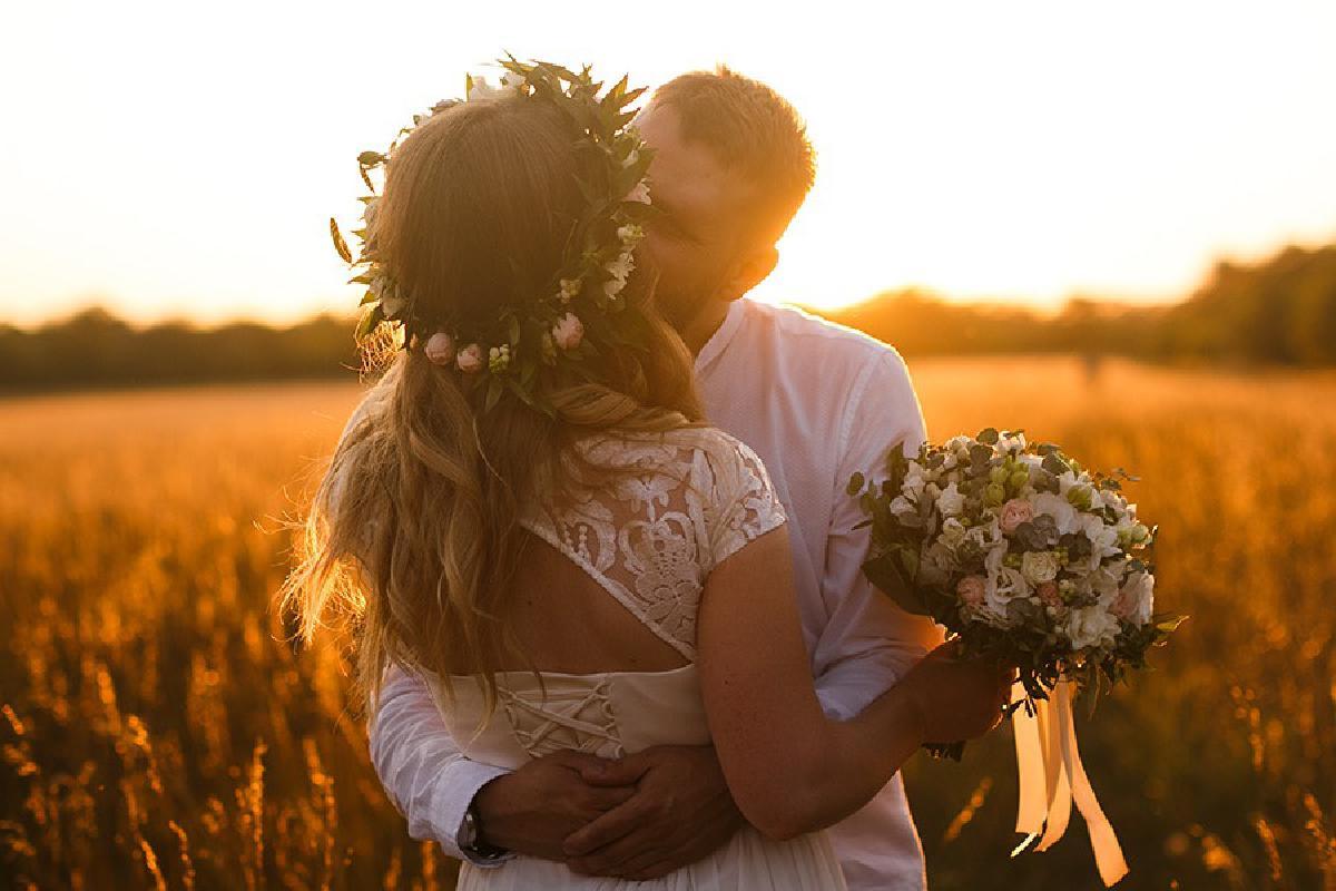 Ehepaar küsst sich auf Feld im Sonnenuntergang