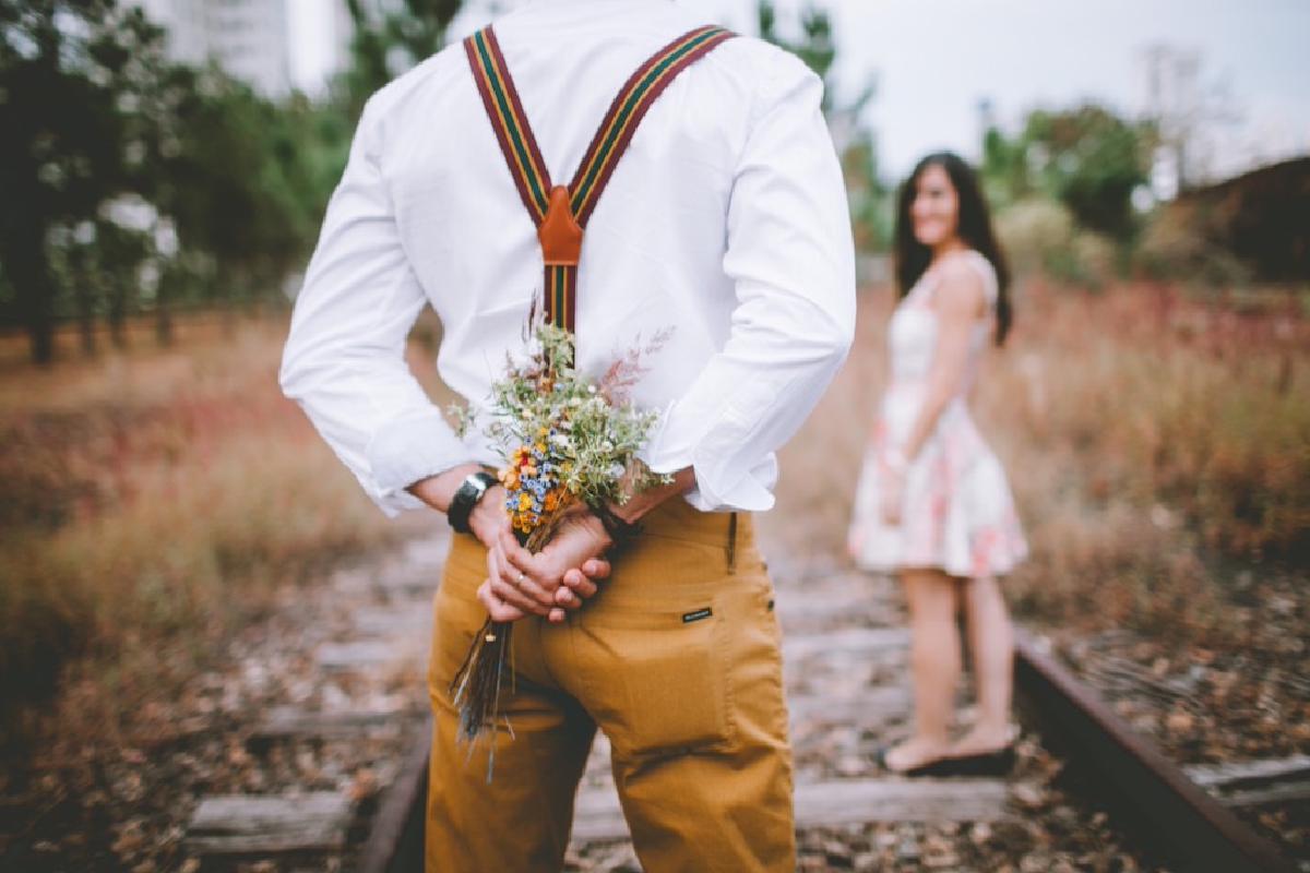 Mann versteckt hinter seinem Rücken Blumen vor einer Frau