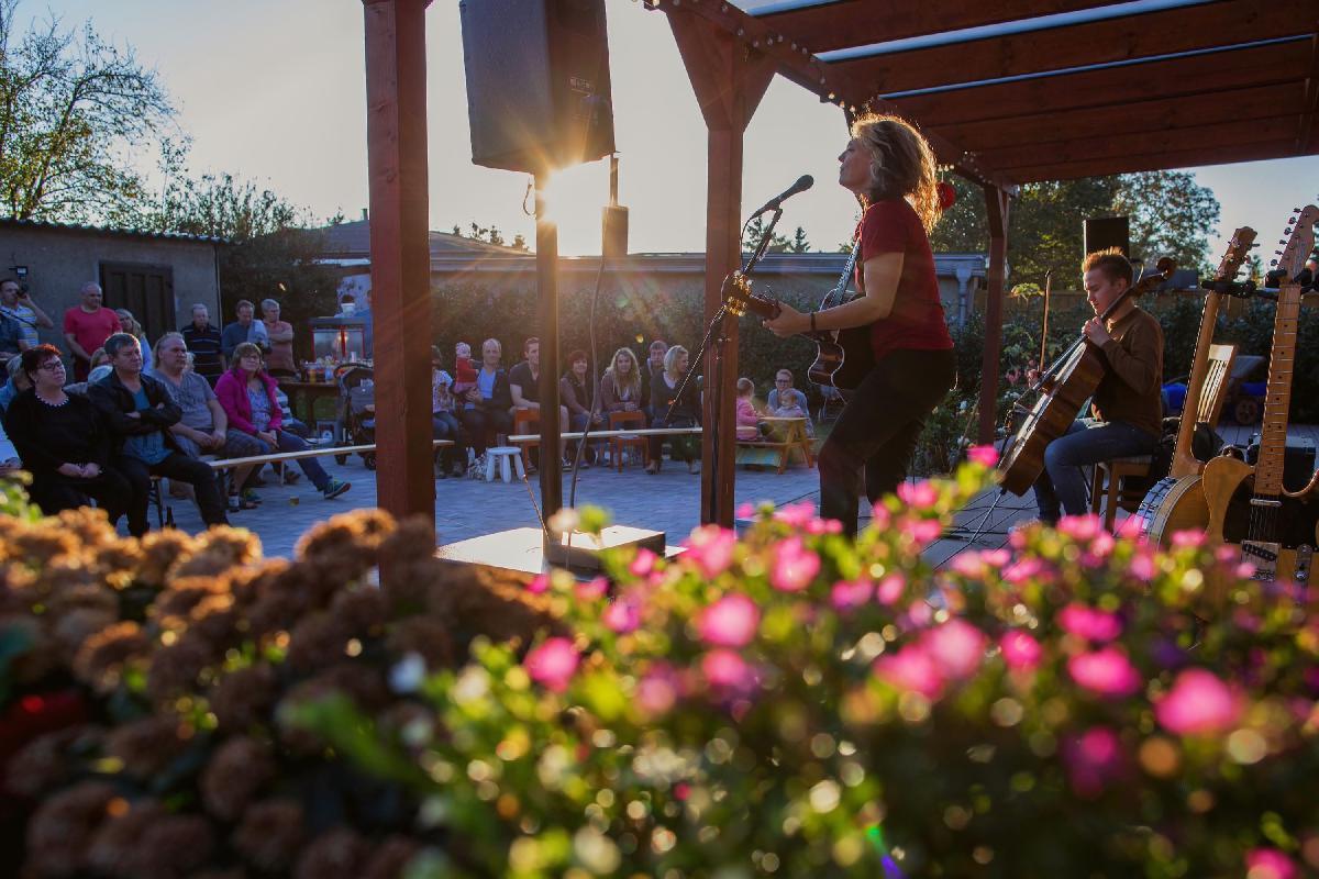 Band spielt draußen Konzert vor bestuhltem Publikum