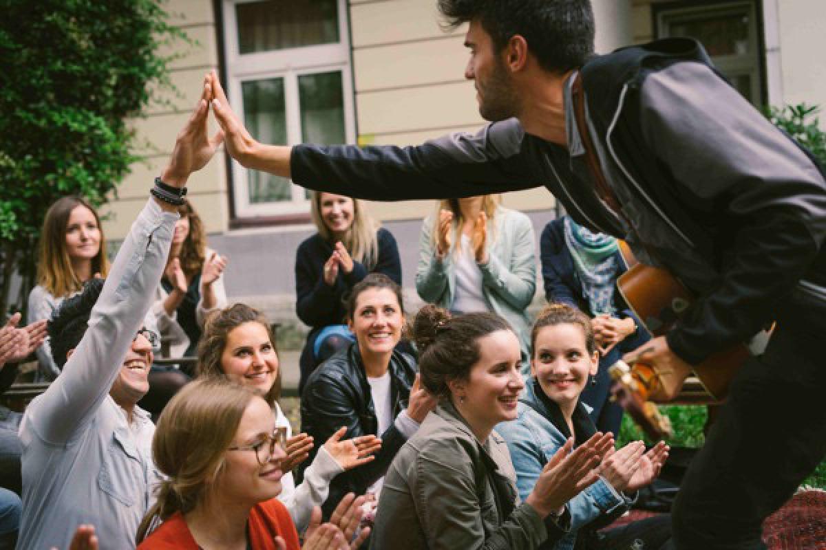 Künstler klatscht während eines Konzerts mit Publikum ab