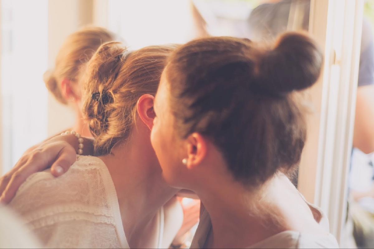 Zwei Frauen flüstern sich etwas ins Ohr