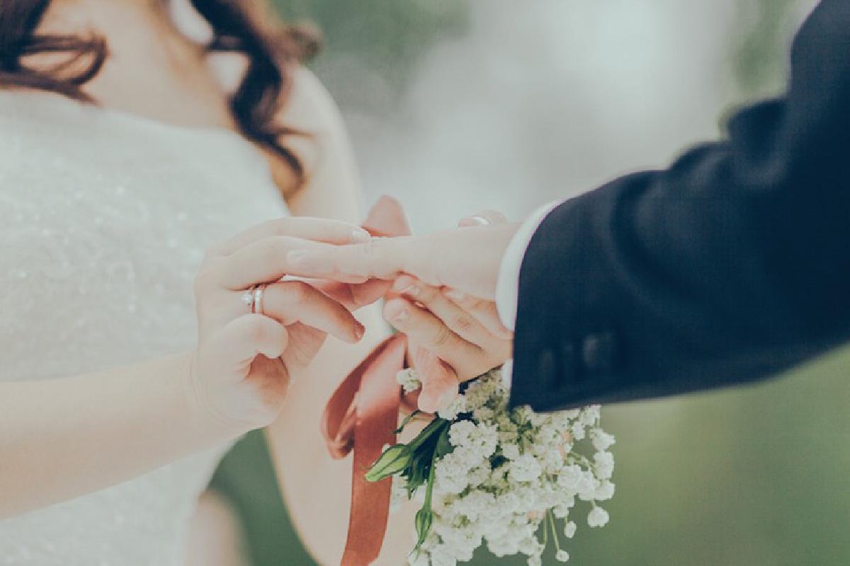 Braut steckt Bräutigam einen Ring an