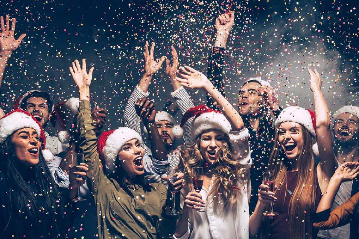 Frauen mit Weihnachtsmützen werfen Konfetti in die Luft