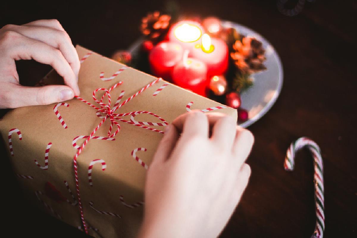 Weihnachtsgeschenk wird verpackt mit Kerzen im Hintergrund