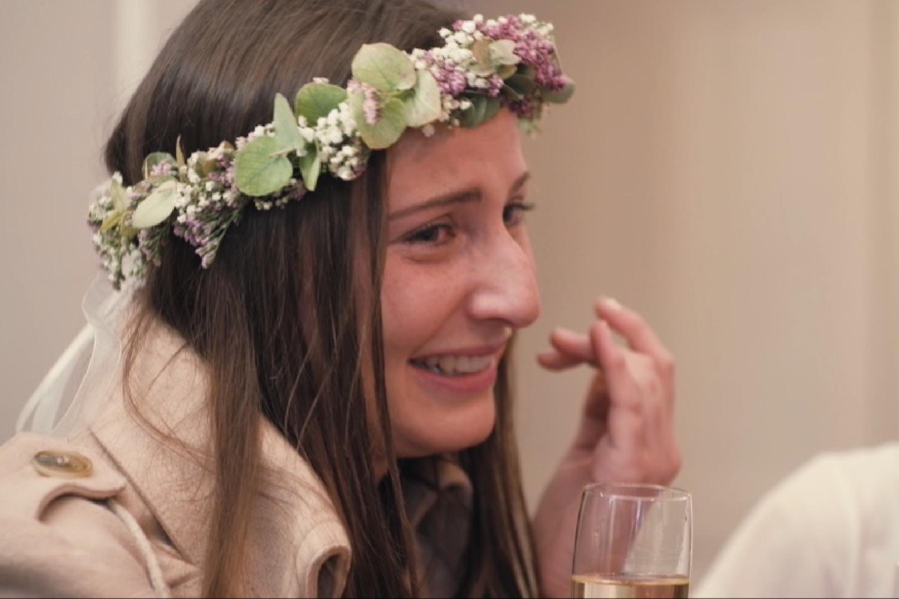 Braut lächelt weinend mit Blumenkranz und Sektglas