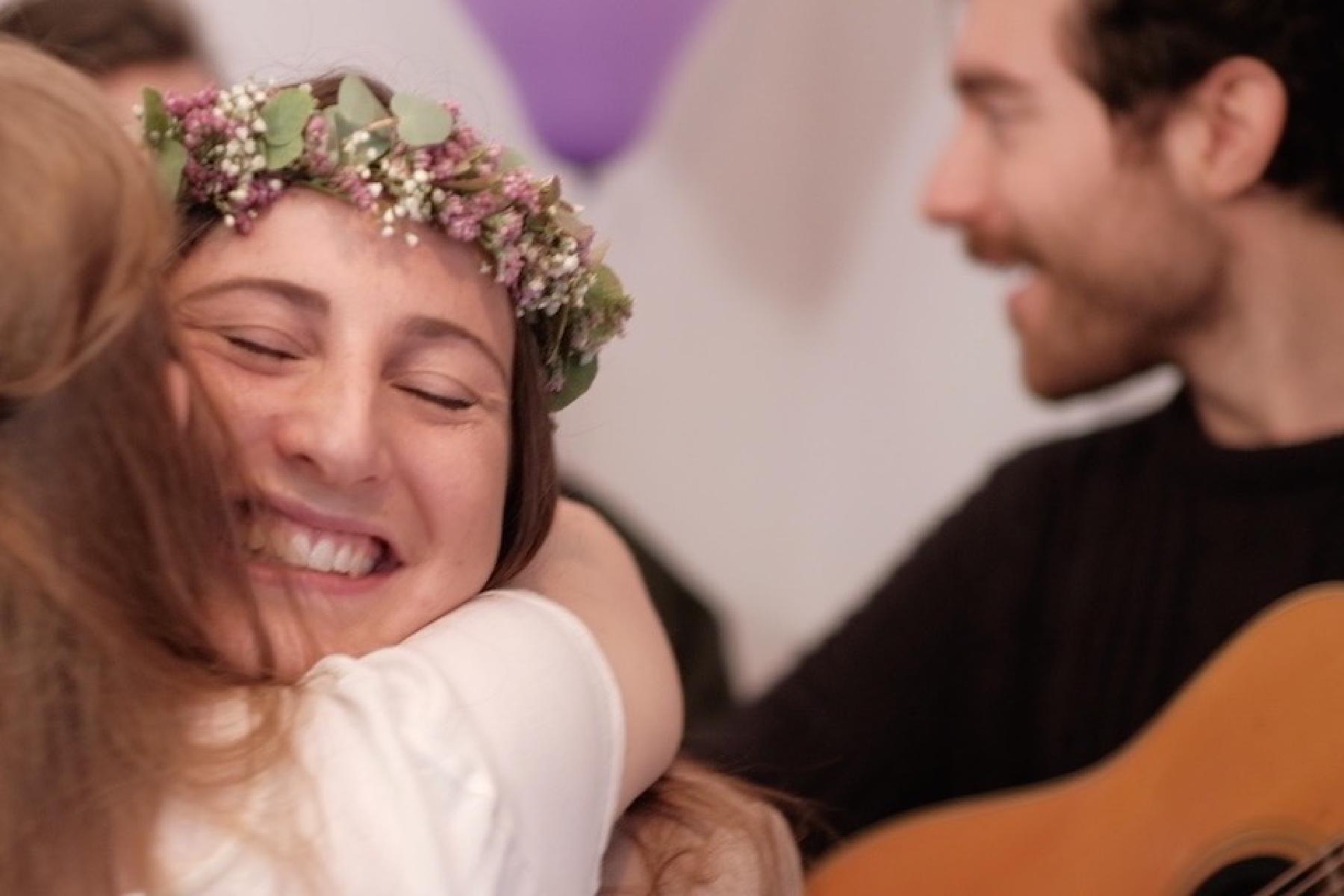 Trauzeugin umarmt Braut mit Amistat im Hintergrund