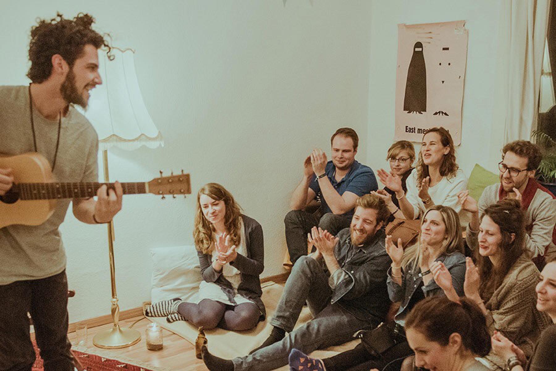 Künstler spielt Wohnzimmerkonzert vor klatschendem Publikum