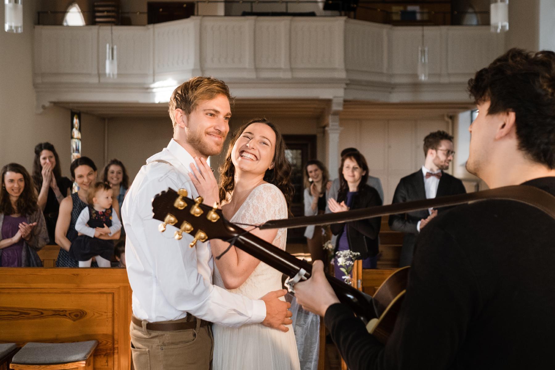 Braut und Bräutigam hören Musiker zu in Kirche
