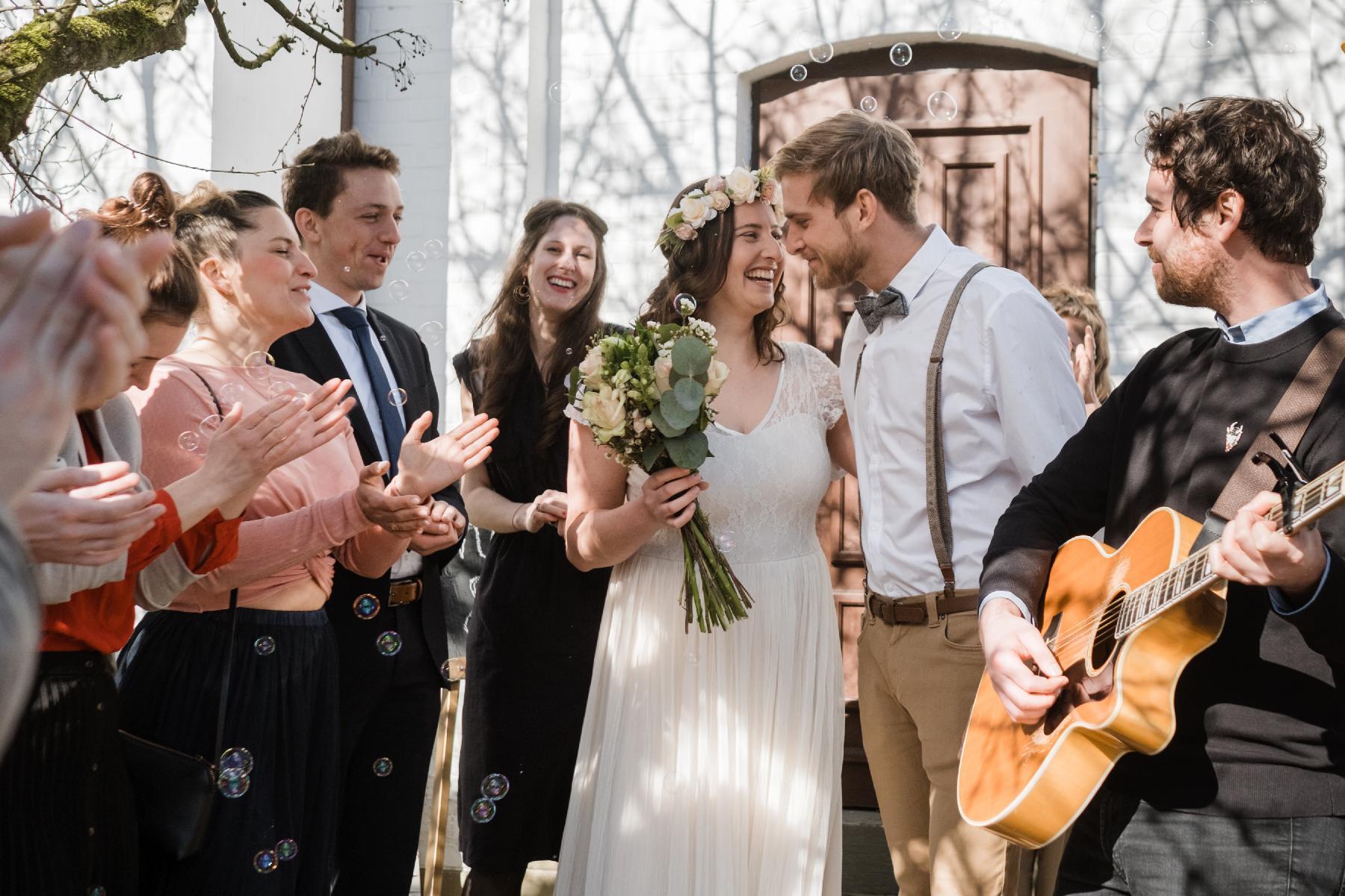 Ehepaar vor Kirche mit Musiker