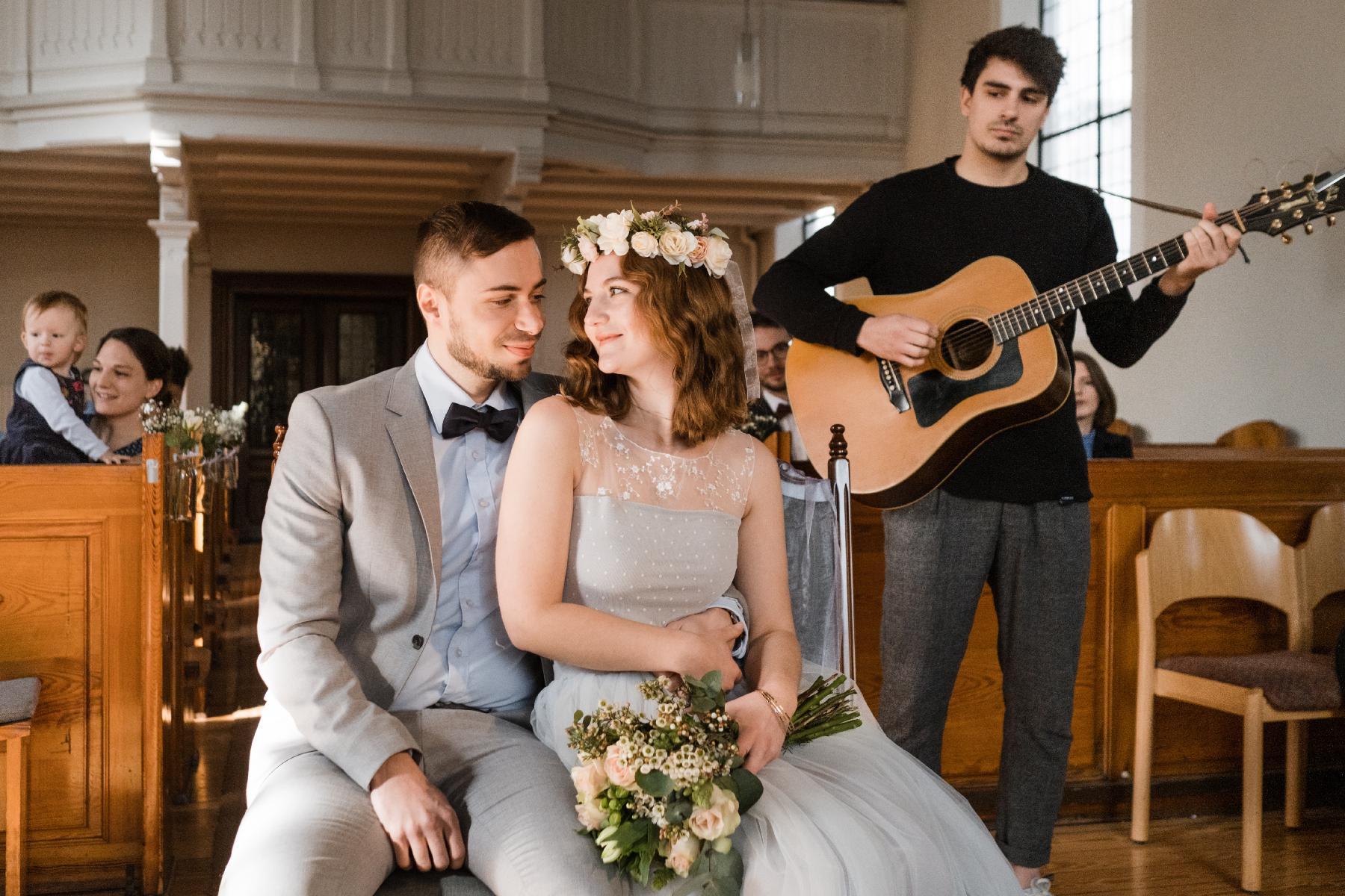 Ehepaar sitzend in Kirche mit Sänger im Hintergrund