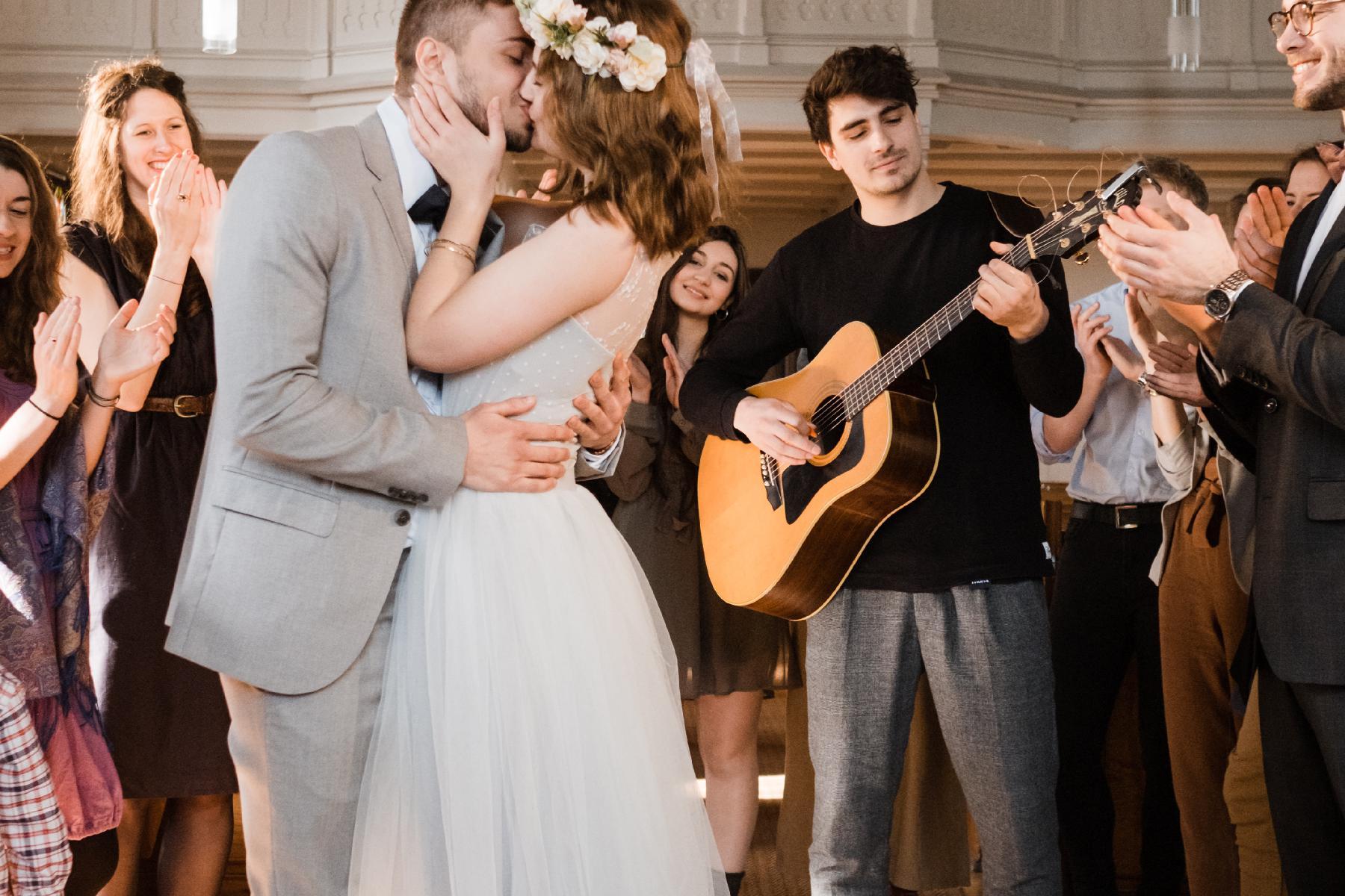 Ehepaar küsst sich vor Gitarrist in Kirche