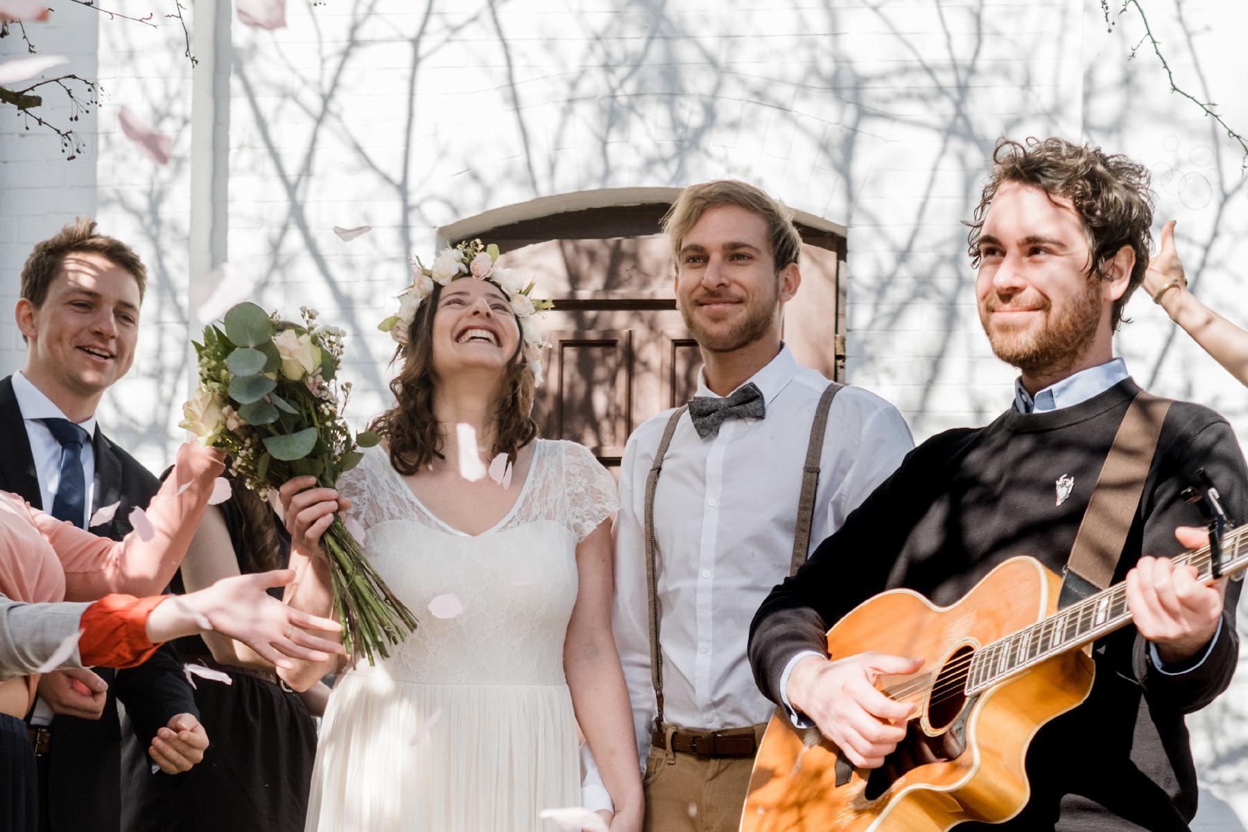 Ehepaar bei Auszug aus Kirche mit Gitarrist