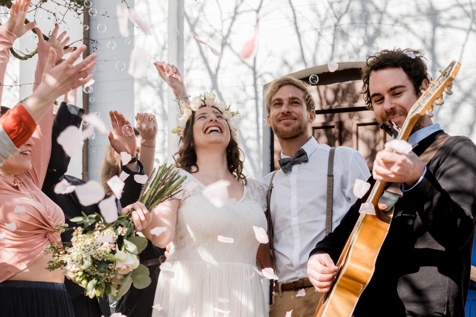 Ehepaar und Musiker bei Auszug aus Kirche mit Rosenblättern