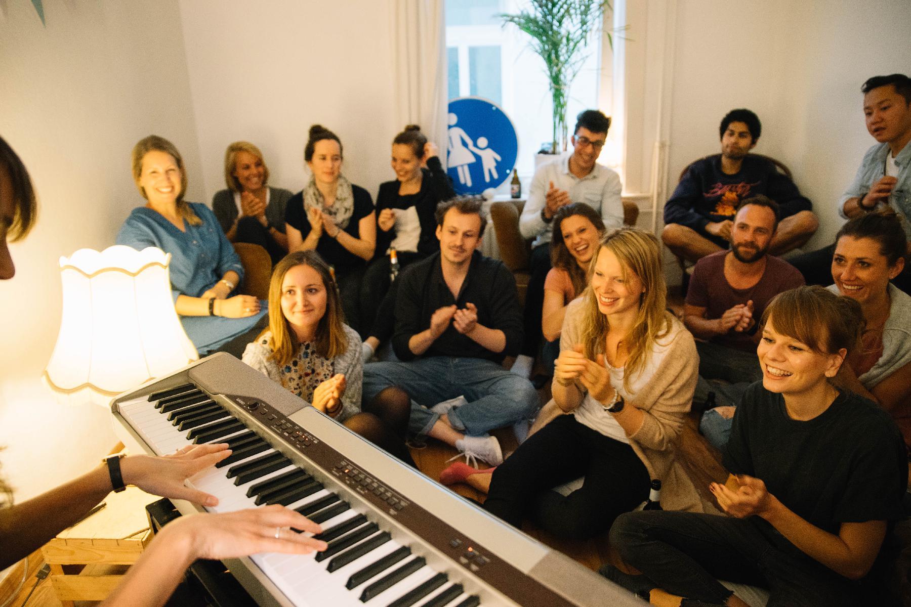 Publikum klatscht bei Wohnzimmerkonzert vor Klavier