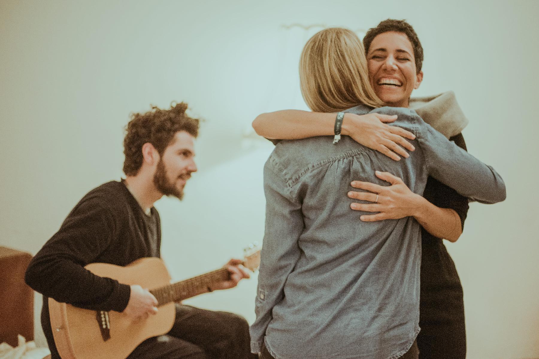 Frauen umarmen sich mit Matteo und Gitarre im Hintergrund