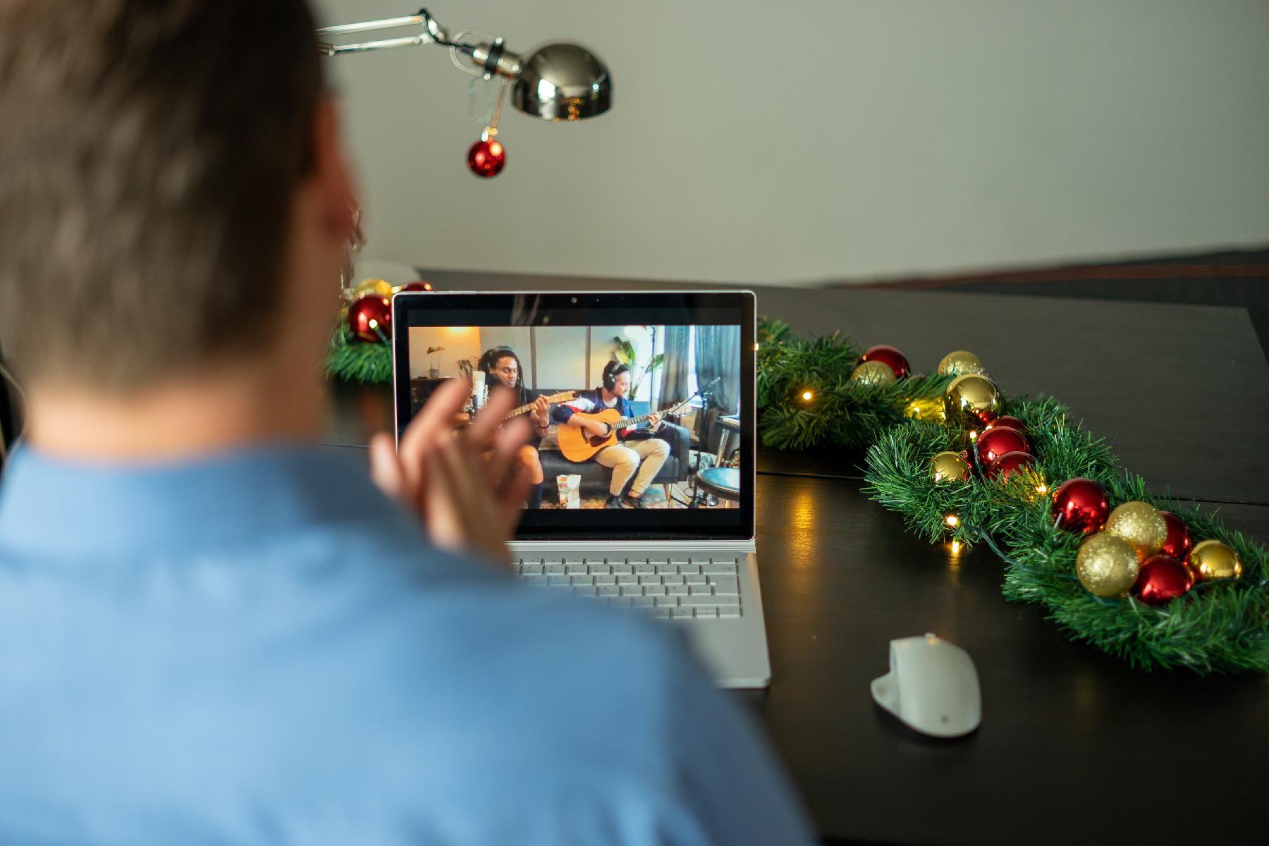 Mitarbeiter sieht Livestream Konzert auf virtueller Weihnachtsfeier